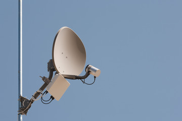 Wireless dish on metal pole with clear blue sky