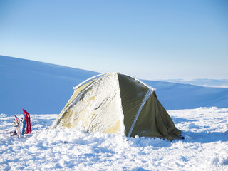 Snowshoes and tent against the blue sky.