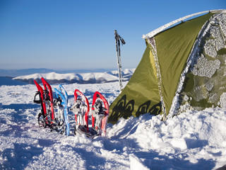 Snowshoes and tent in the mountains.