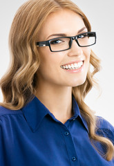 Happy smiling businesswoman in glasses, on grey
