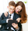 Online shopping. Happy smiling couple using PC tablet