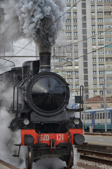 Old classic train leaving the station in clouds of smoke