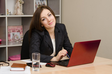 Business woman smiling at the computer
