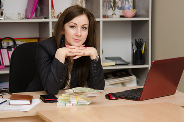 Business woman at desk with a stack of money