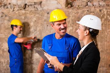 Bauarbeiter und Bauleiterin auf Baustelle