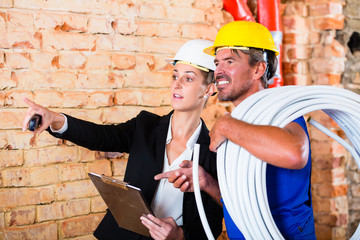 Bauarbeiter und Architekt auf Baustelle mit Schlauch