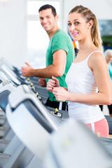 Mann und Frau auf Stepper im Fitnessstudio