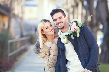 Portrait of a happy young couple holding a rose and embracing
