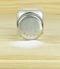 A glass salt shaker with metal lid and spilled salt