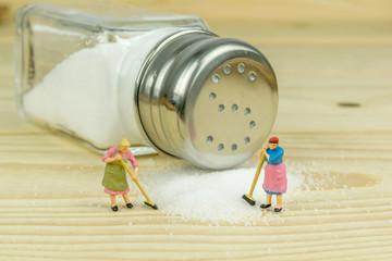 Miniature toy housewives figures cleaning up spilled salt
