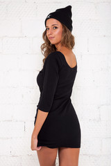 A young girl in a black dress stands back and looks