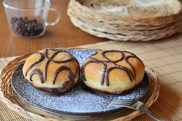 Traditional  doughnut with chocolate on the brown plate