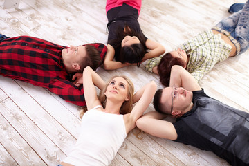 group of young people lying on the floor in a circle together