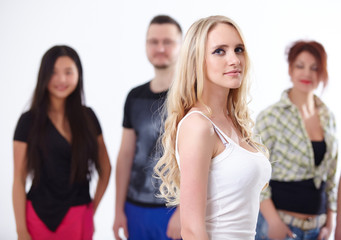 young blond woman on the background of a group of students