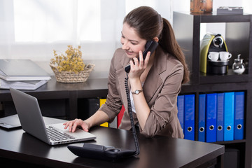 business woman with landline phone and notebook