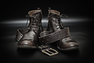 High leather boots and men's leather belt on a black background