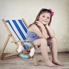 Little girl sitting on the sunbed