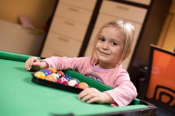 La petite fille derrière une table de billard
