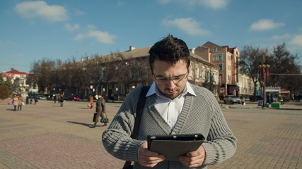 Young man using electronic tablet in the city center in the