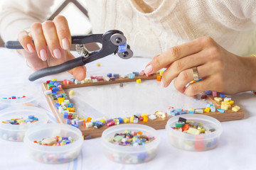 Woman decorating photo frame with colorful glass mosaic