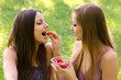 Two beautiful girls eating strawberries in the nature on sunny s