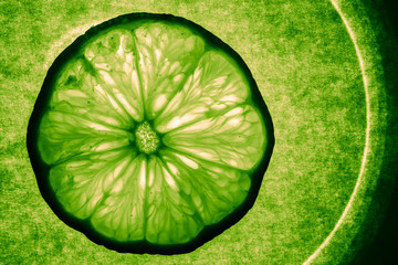 Abstract macro slice of lime against green background