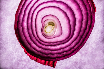 Cross section slice of red onion against textured background