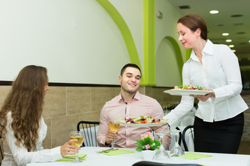 Female waiter serving guests table