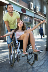 Husband taking spouse on wheelchair