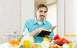 man doing veggy lunch with cookbook