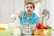 Caucasian handsome man does veggie soup