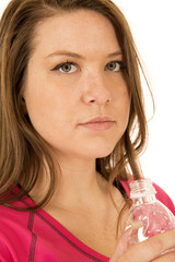 female model holding a bottle of water with a serious expression