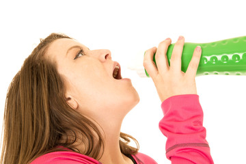 Young woman drinking water from a green water bottle