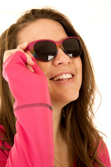 Happy young female model sporting pink sunglasses