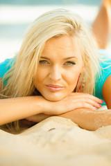 Beautiful blonde girl relaxing on beach