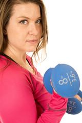 Portrait of a female model lifting blue barbells