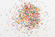Colorful round sprinkles spilled on white background, isolated