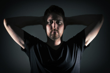 Man posing with angry face and dark background with hard lightin