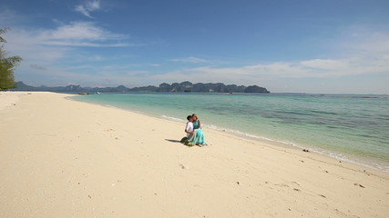 guy sits on stone with asian girl on his knees on sand beach at