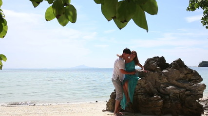 asian blonde girl and handsome guy kiss stand near rock on sand