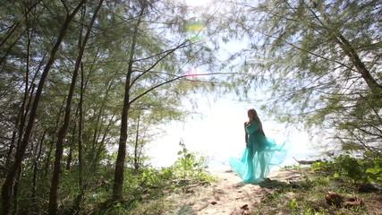 asian girl gorgeous blue dress blows under wind near small palms