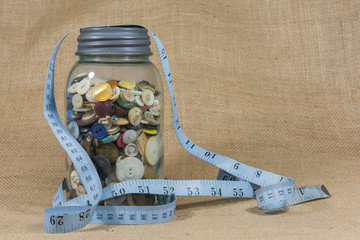 Jar of buttons draped with seamstress measuring tape