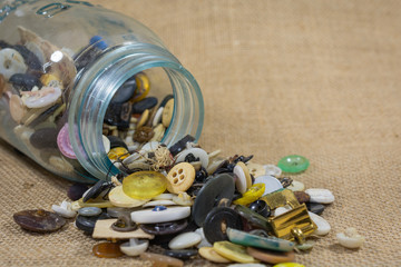 Jar of buttons emptied onto burlap