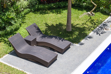 Two beach chairs next to a swimming pool in a tropical garden