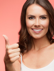 Portrait of happy woman showing thumb up gesture, on red