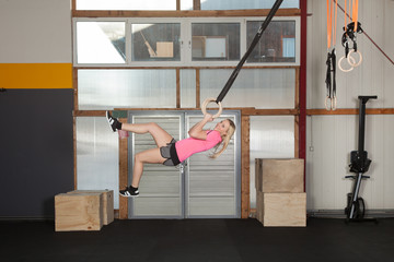 Woman swinging in the air with gymnastics rings - fitness traini