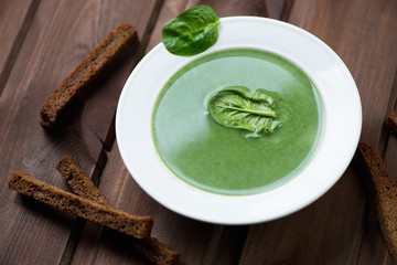 Glass plate with spinach cream-soup on a dark wooden background