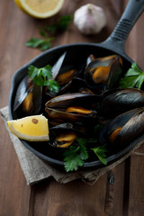 Boiled mussels with lemon, parsley and garlic, selective focus