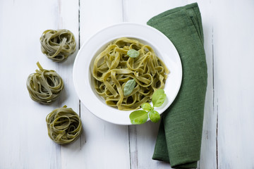 Tagliatelle with green basil leaves, white wooden background