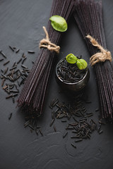 Raw black rice noodles, high angle view, vertical shot
